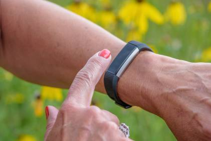 A woman using her fitness wristband.