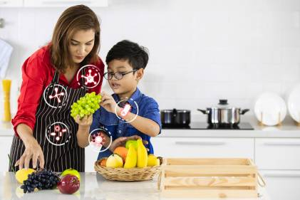 A mother and son i n the kitchen selecting fruits with icons of probiotic bacteria.
