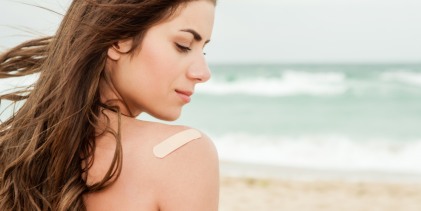 A woman on the beach with a bandage on her shoulder
