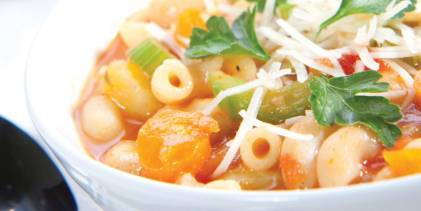 a hot bowl of soup with vegetables and pasta