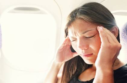 A woman seated on an airplane rubbing her temples to reduce anxiety.