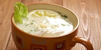A mug of avgolemono soup with garnish