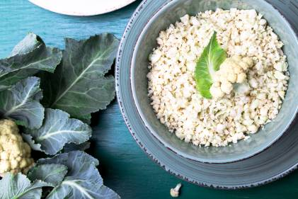 Cauliflower rice in a blue bowl on a blue table next to a head of cauliflower with leaves.