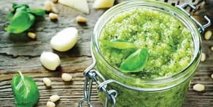 A canning jar of fresh basil pesto with garlic and cheese