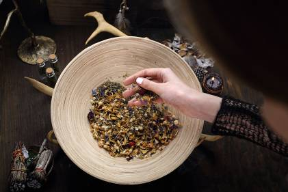 a woman mixing medicinal herbs near a smudge stick and a candle