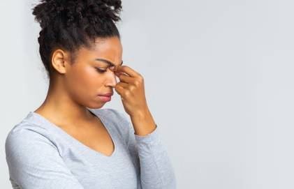 A young black woman holding the bridge of her nose due to sinus pain.