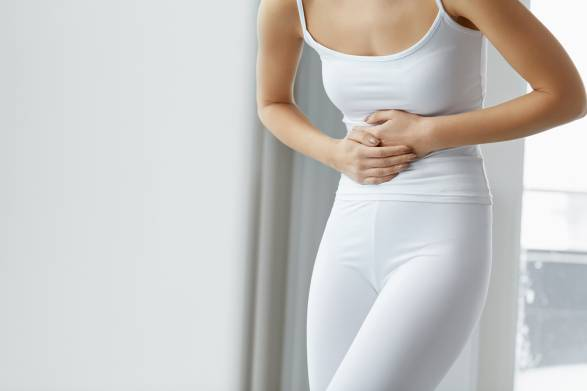 A woman in all white holding her stomach in pain.