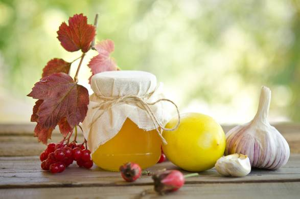 Honey and other natural medicine for winter flu, on a wooden table.