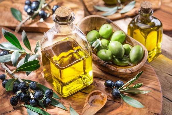 Olive oil, Berries on a branch and olives in a bowl placed on a wooden cutting board.