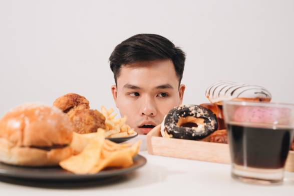 Young man having cravings for donuts, hamburger, chicken with fries.