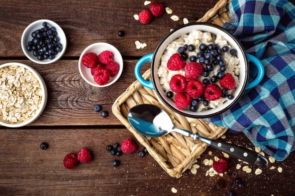Oatmeal, oats and berries on a rustic wooden table.