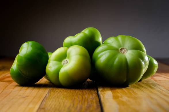 Green tomatoes on a wooden table