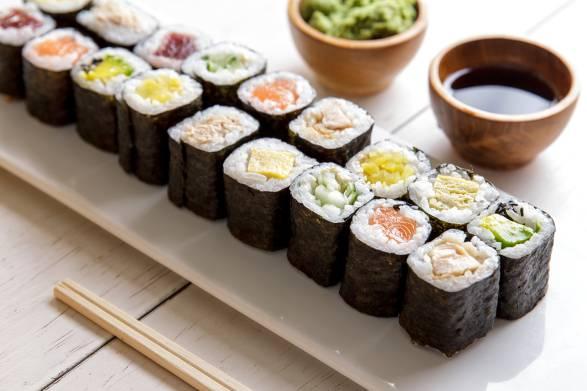 Mini maki sushi platter on white wooden table.