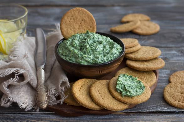 Vegan green spinach dip with on a wooden board with oat crackers,