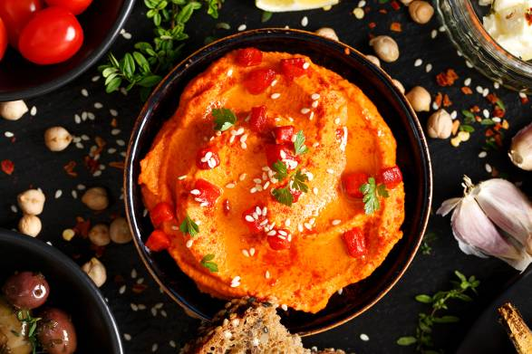 Top view of Red Hummus in a dark colored bowl surrounded by ingredients and foods to dip. Dark background.