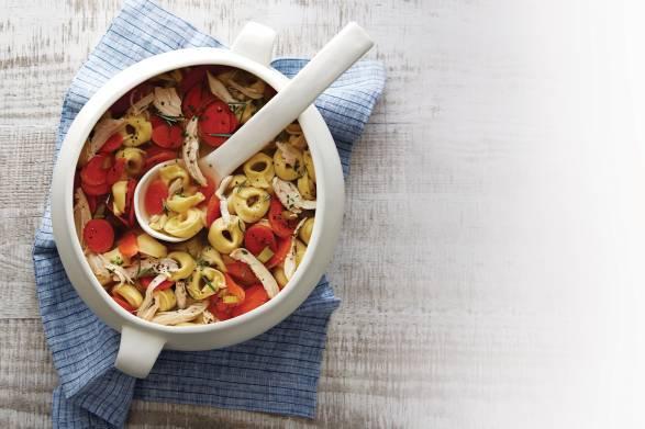 Chicken tortellini soup in a white soup crock.