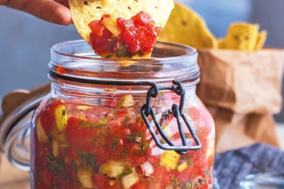 A tortilla chip dipped in a jar of fermented garden salsa