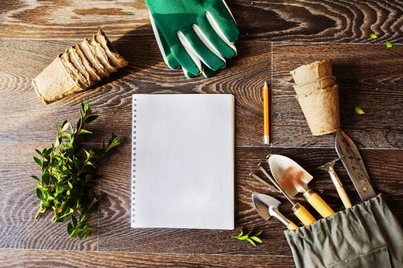 Note book, peat pots and tools laid out for spring garden planning.
