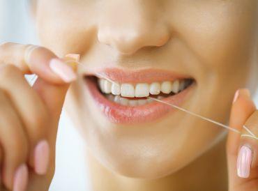 Woman flossing her teeth.