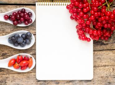 wild berries on wooden table with notebook