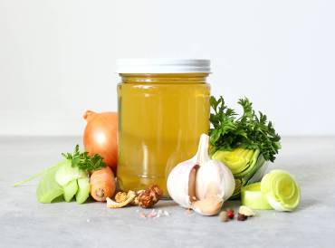 a jar of broth and some prepped vegetables