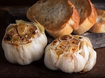 heads of roasted garlic with slices of toasted bread.