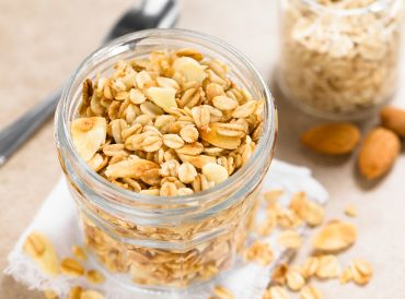 Coconut Almond granola in glass jar, ingredients and spoon in the background.