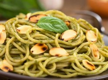Dish of whole grain pasta, pesto and slivered almonds.