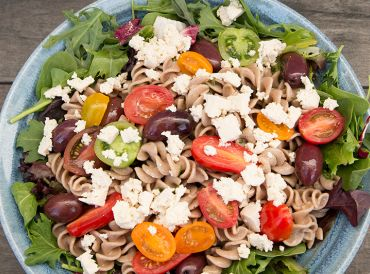 A bowl of pasta salad topped with vegan tofu feta