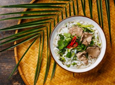 Pho Bo vietnamese Soup with beef on bamboo tray on wooden background.