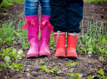 View of rubber boots, woman and child in a garden