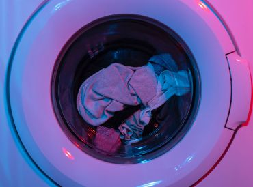 Clothes in a front loading washing machine illuminated with red and blue hued lighting.