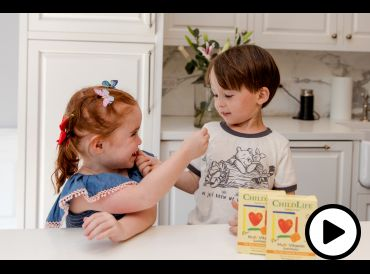 two toddlers sharing children's vitamins